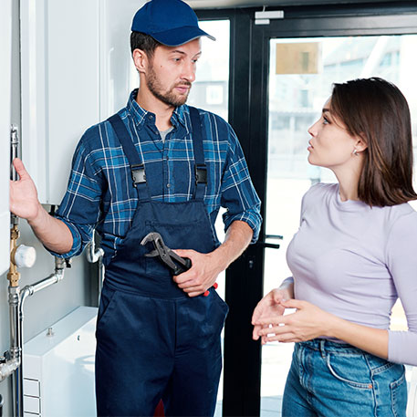 A Plumber on a Blue Jumpsuit Talking to a Young Lady